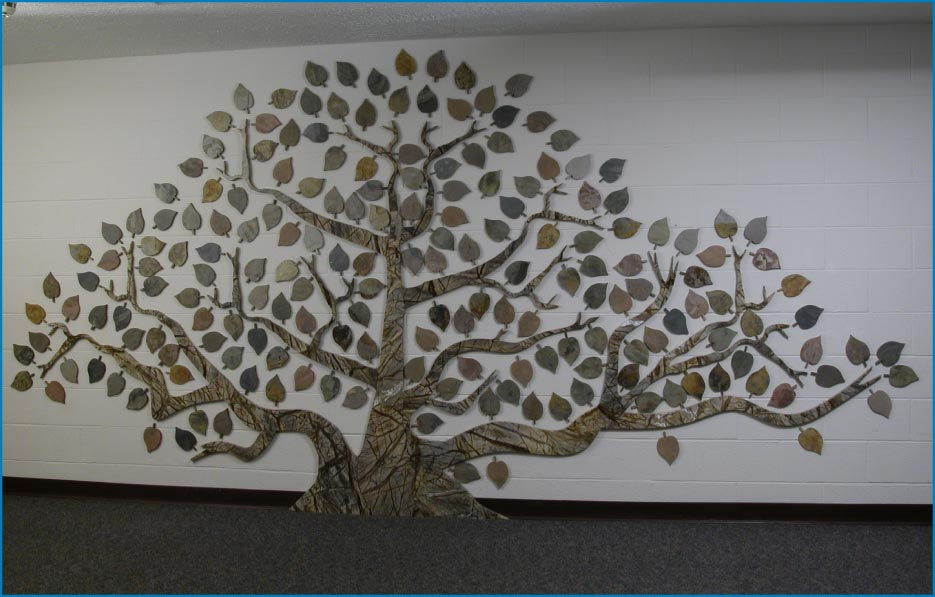 "Rocky Mountain Stone has produced a number of intricately cut ""giving trees"" using their waterjet saw. This tree features a rainforest green marble trunk with colorful Indian Autumn slate leaves."