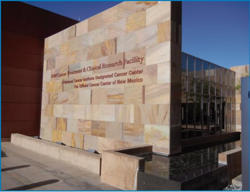 The UNM Cancer Treatment and Research Facility entrance wall includes a water feature.