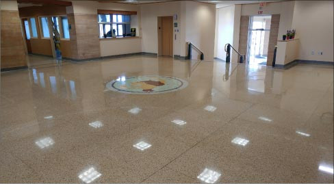 After stripping the finish, grinding and polishing, the restored terrazzo floor is restored to its former glory.