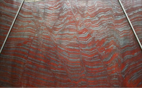 In this Iron Red slab, the stripes of intense red and sparkly grey are accumulations of iron oxide and sand sediment that accumulated  only during a specific era in the earth's geologic history.