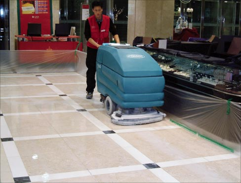 Floor polishing maintenance in progress for a commercial contract. Even with routine re-polishing, eventually any floor will need honing.