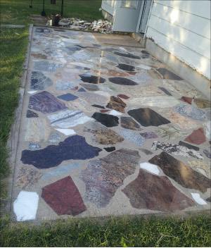Mixed granite and marble scraps in irregular shapes and sizes give this colorful patio floor a fieldstone look. Recycling and repurposing can save millions of tons of good stone from being dumped in waste piles and landfills.