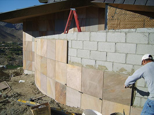 Adhering Panther Sandstone to a concrete retaining wall at the private residence featured on page 37.  The installer is following proper adhesion methods as specified by CTaSC.