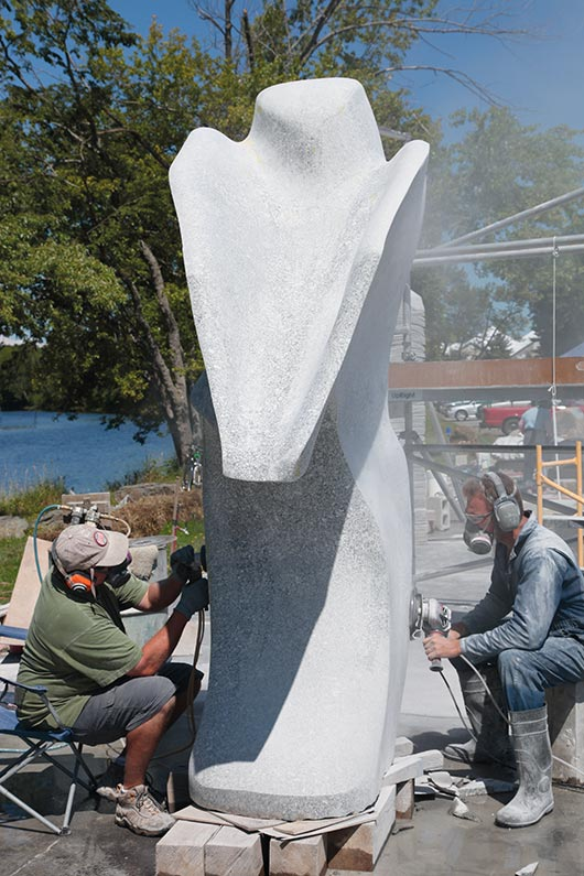 Andreas Von Huene (at right) grinds and shapes a curve, and assistant Richard Reichenbach wet polishes the in-progress sculpture