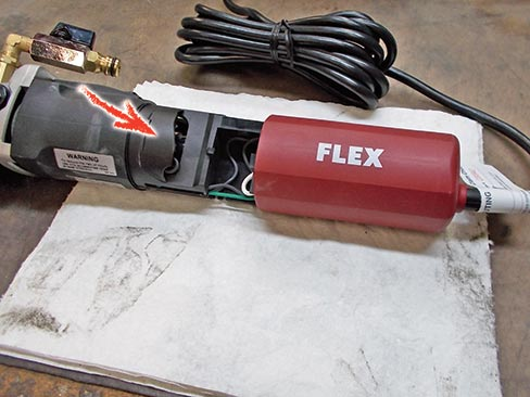 Fig. 1. Carbon brush locations vary on different tool models and makes, but all are usually located under a protective housing, accessible by removing screws on the cover. The above example shows the Flex LW-1503 with cover/handle removed; the brushes lie behind the protective inner cover indicated by the red arrow.
