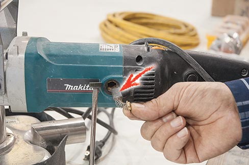 Carbon brush locations on a Makita (NEED MODEL#) lie behind easily removed buttons located just in front of the handle. Be careful–they are spring retained, as shown in the above photo. This model is attached to a Scarab machine; it's not necessary to remove the cover to access the brushes.