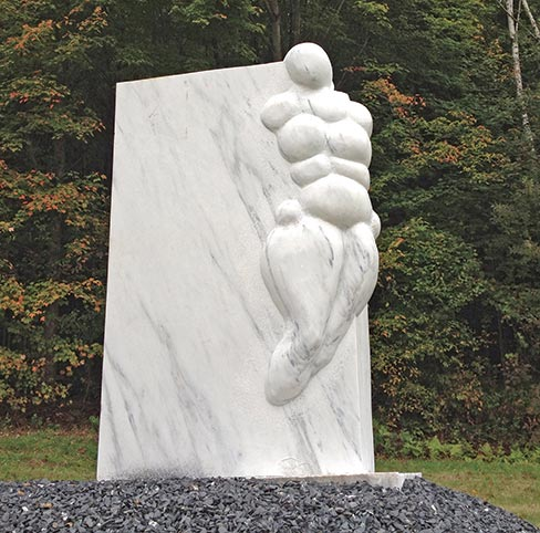 "A human figure emerges from a polished slab of Danby White Marble, carved by Liliya Pobornoikova from Bulgaria. The sculpture is titled ""Dance."""