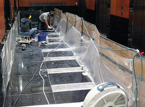 Boua and Jaron Wiley resurfacing, honing and polishing black galaxy granite tiles at the Fox Tower Building in Portland.